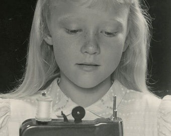 Vintage photo Little Blond Girl Sits at Toy Sewing Machine