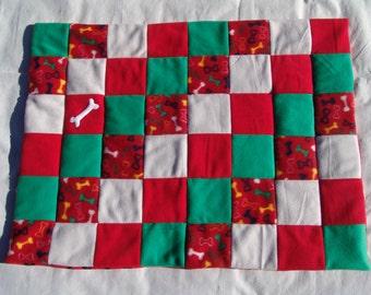 Medium fleece dog blanket - multi colored bones on red