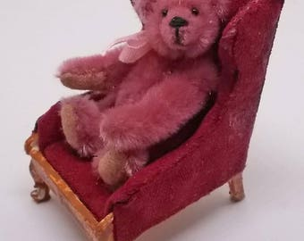 Dollhouse Miniature Antique Style Bear in Distressed red velvet seat.