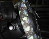 Peacock feather steering wheel cover. Blue and green feathers. Seat belt covers and key fob options. Lined cover.