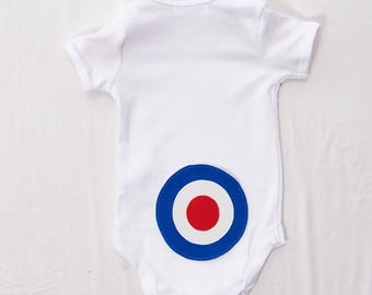 Hand Sewn Blue Target on the bottom of a white babygrow