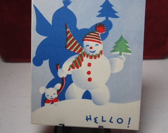 Colorful 1940's unused christmas gift card snowman holding a mini christmas tree and walking with a dog on leash , large shadow behind him
