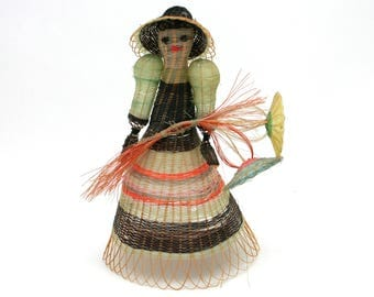 Vintage woven straw girl doll in dress with hat and flowers, folk art sculpture, weaving, delicate, green, yellow, orange, black, ethnic