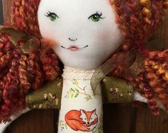 Molly the red headed rag doll wearing fox print and orange skirt