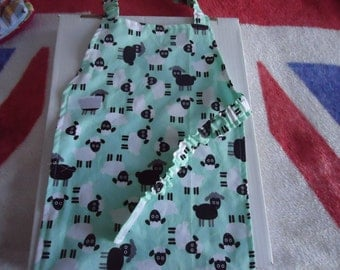 Delightful Sheep / lamb print craft/ baker apron for a child.  Lined apron.  Mint green colour with black and white sheep.  Velcro closures.