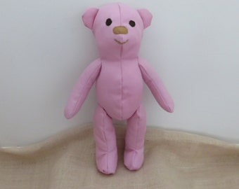 Bella. The cute, cuddly, pink material, soft, handmade Teddy Bear with a purple wool scarf and a white with green spots skirt.