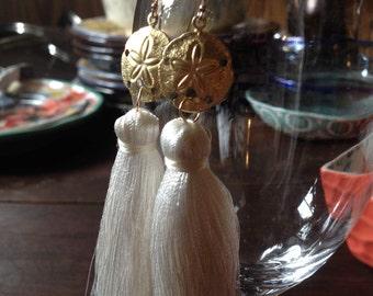 Fat white silk tassel earrings with golden sand dollars. 14k gf French ear wires. Thick tassel earrings.