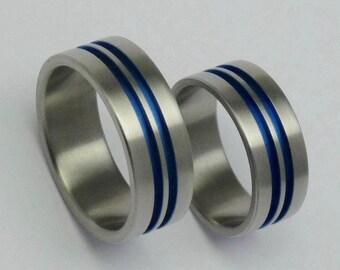 Pair of anodized titanium engagement rings. Titanium weddingrings. Anodized flat titanium bands.