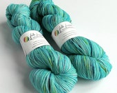 Hand dyed yarn.  100g of speckled hand painted 75/25% superwash BFL/nylon sock weight yarn, fingering, 4ply. Bobbing Along, blue, speckles