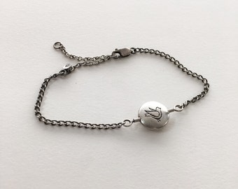 silver thaumatrope bracelet, bird and cage spinning charm