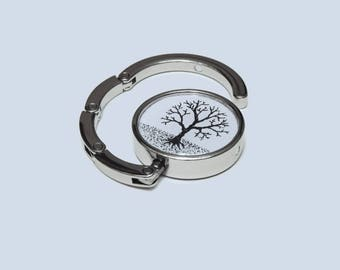 Bare Tree folding handbag hook. Hand-drawn illustration, sealed inside a foldable, pocket-sized accessory, to hang your purse under a table.
