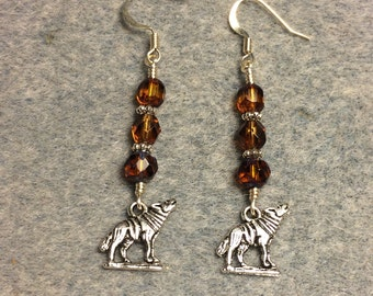 Silver howling wolf charm dangle earrings adorned with amber brown Czech glass beads.