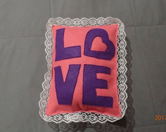 Pink pillow with L-O-V-E and lace