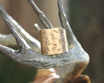 Brass Cigar Band - brass sheet cut into a cigar band shape and stamped with letters.