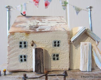 Little driftwood cottage with bunting beach hut and paddle board