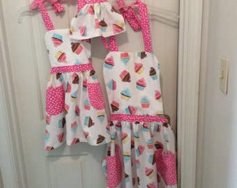 Mother, daughter, doll matching aprons
