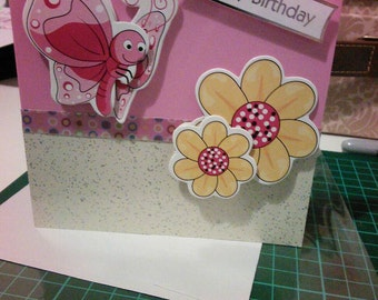 Stunning handmade birthday card with glossy pink and glitter split background, flower and butterfly embellishments. FREE POSTAGE!