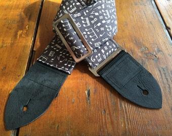 Stylish musical handmade guitar strap -- cream notes on a dark brown background