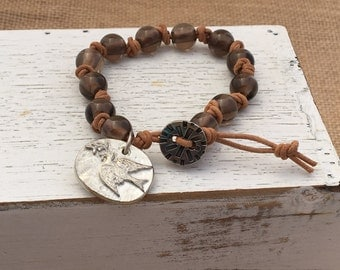 """Single Wrap Round Leather Knotted Bracelet with 10mm Smokey Quartz beads and Dove """"Hope"""" medallion."""