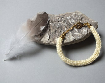 Pale yellow knitting wool and brass bracelet
