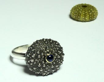 Silver sea urchin ring with sapphire in golden setting. Casted silver 925 sea urchin with sapphire in 14 carat golden setting ladies ring.