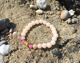 Bracelet soft pink beads with a golden colored budha bead
