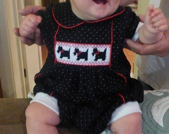Black spotted knit romper with red piping and smocked scottie dogs.