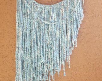 Wool yarn wall art on cactus wood