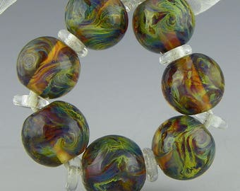 a set of 7 translucent rounds done in reactive glass and encased in clear handmade lampwork glass beads - Cauldron