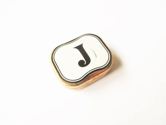 Initial J tin: Charming, very small antique gold coloured tin with white enamel top and black printed initial capital J motif