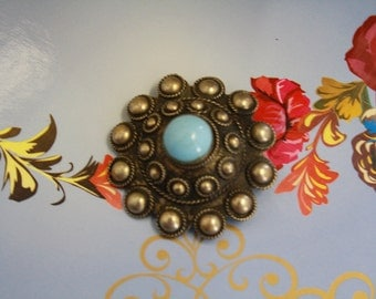 Shaped vintage metal brooch with turquoise stone