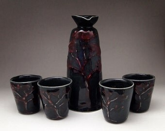 Sake set  - porcelain bottle with four cups, grey black with red relief tree  Anita Reay