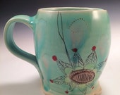 Aqua mug, large, with blush yellow flower and pink middle.