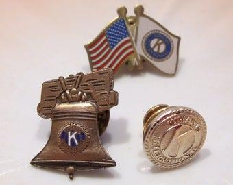 Kiwanis International Group of Three Pins U.S. and Kiwanis Flags, Liberty Bell with Kiwanis Emblem and Gold Kiwanis International Pin