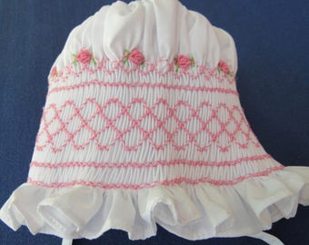 Hand smocked baby bonnet with delicate rose buds and geometric designs.