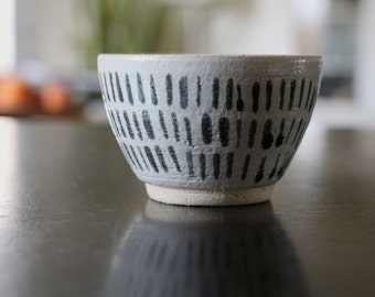 Coffee cappuccino in white ceramic bowl with black patterns, handmade