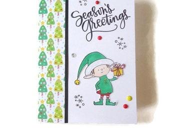 Seasons Greetings - Christmas elf sending merry greetings your way! Handmade Christmas card, adorable elf, Xmas trees, bright colors.