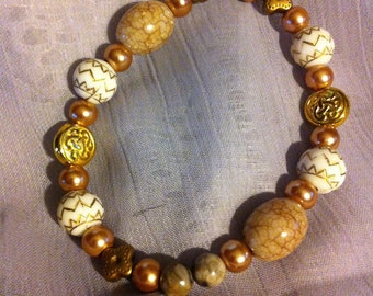 Shades of brown stretch beaded bracelet with Celtic knot beads.