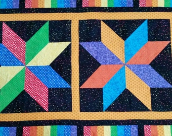 Baby or lap quilt in primary and secondary colors pieces in large stars.  Black with dot complimentary fabric and sky blue backing.