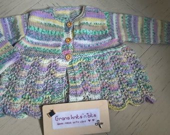 a hand knitted multi coloured girls cardigan with wooden buttons