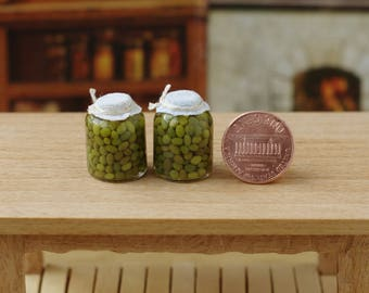 Canned olives in miniature cans. Miniature marinated jars for a doll house. Miniature green olives. On a scale from 1/12.
