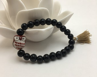 Jet Black beaded flexible bracelet with a Ceramic Owl and Beige Tassel.