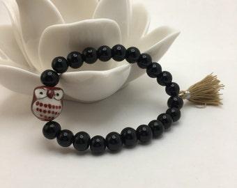 Jet Black beaded flexible bracelet with a Ceramic Owl and Beige Tassel.