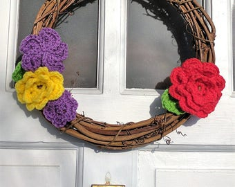 12 inch grapevine wreath with purple, yellow, and red crochet flowers