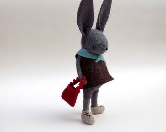 Cashmere Bunny  -  Handmade plush rabbit wearing grey felt pants and a brown felt tunic with a turquoise neck piece, carries a tiny bag.