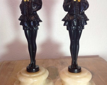 1920s art deco harlequin attire, cold painted spelter female statuettes, white marble base, carved Ivorine face and hands
