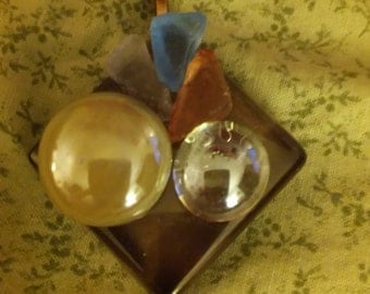 Brown glass disk with two glass disks and rust, blue and purple seaglass pendant