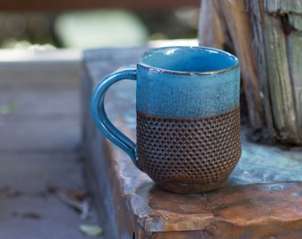 Hand-built mug with a a texture of dots accented by underglaze