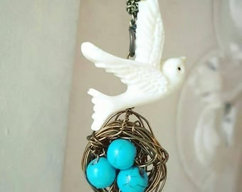 Bronze Bird's Nest Necklace featuring three turquoise eggs and a white as snow Spirit Dove. 18 inches.