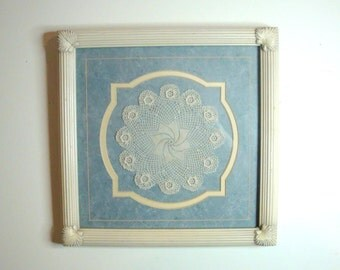 "Vintage framed crocheted doily with a center swirl and roses around the edge. Professionally matted and framed. Outside dimensions 12"" sq"